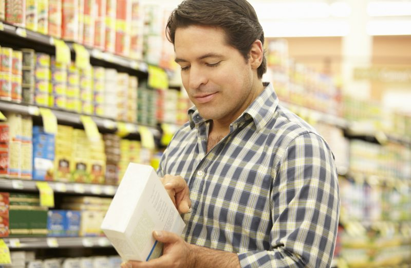 Man shopping in supermarket reading product information