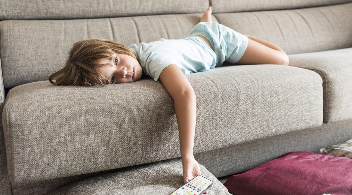 Little girl watching TV on the couch stretched