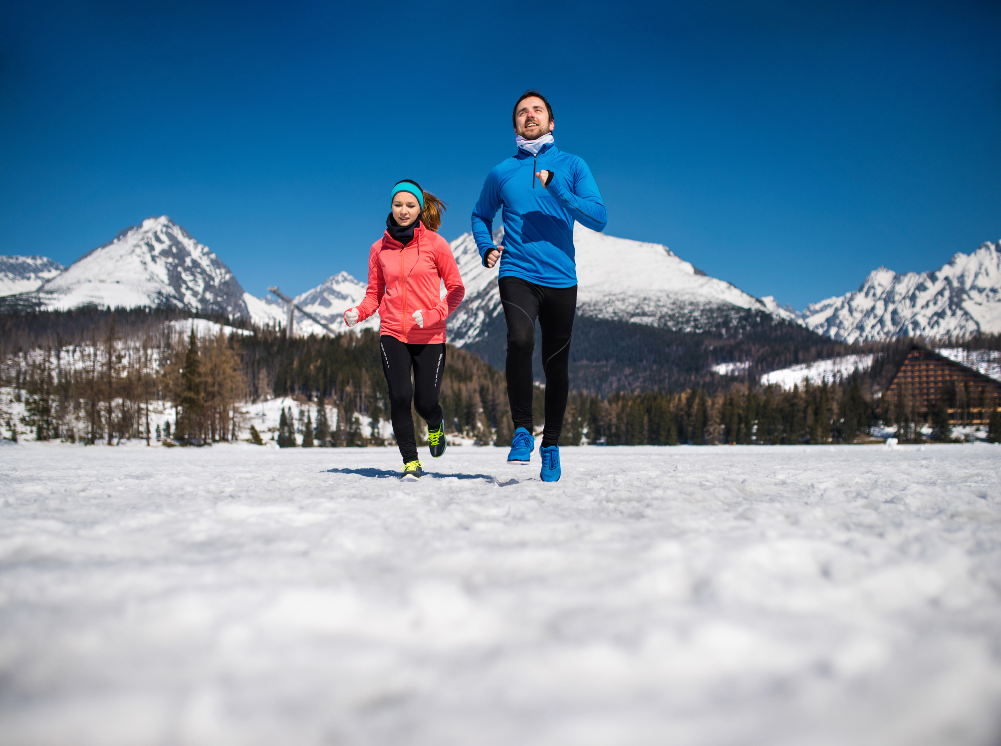 Young couple jogging outside in sunny winter mountains.