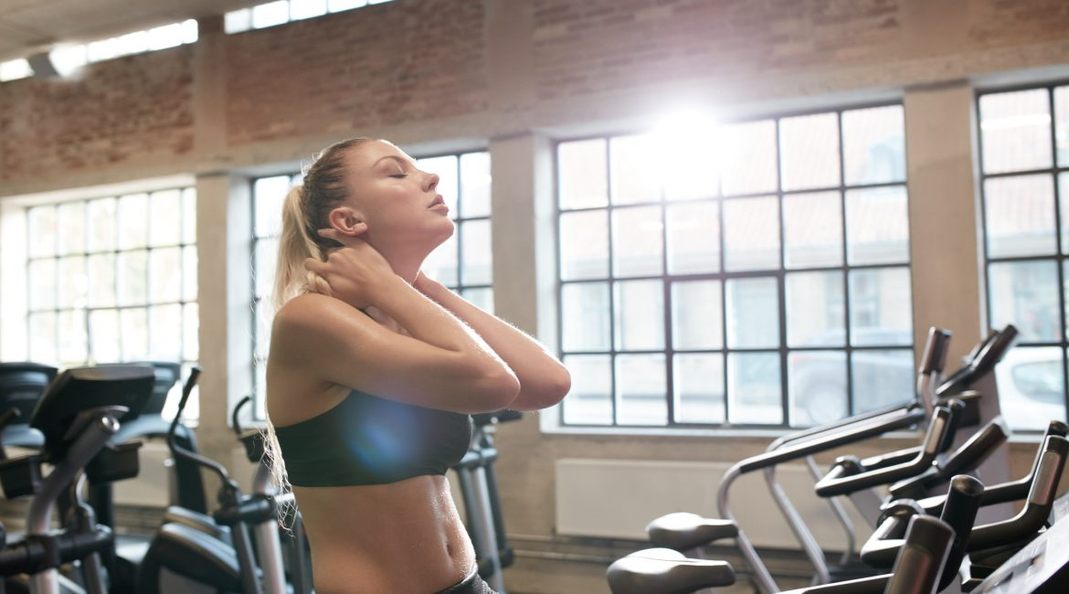 Young Woman Tired After Intense Workout On Gym Bike Relaxing Her Neck Muscles